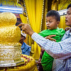 Applying some gold leaf to the sacred Buddha statues at Phaung Daw Oo Paya.