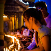 Visitors to Rangoon's Shwedagon Pagoda light candles at dusk.