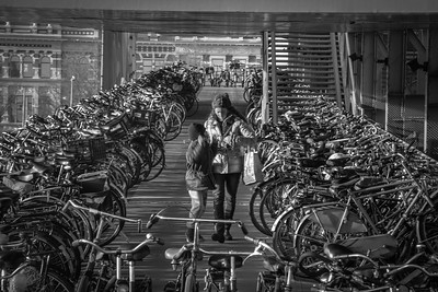 It isn't just budget or fitness conscious people choosing the bicycle as their primary mode of transportation. Citzens of all ages and socio-economic backgrounds  bike the city. Many do not even own cars. Here a mother and her son walk through a multi-story bicycle parking ramp after locking up their bike near Amsterdam Central Station