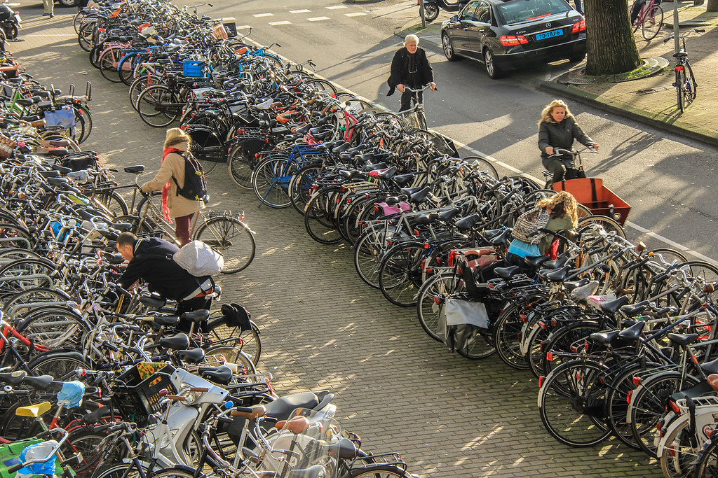 Each year in Amsterdam alone, about 100,000 bicycles are stolen and 25,000 end up in the canals. Pictured are people locking them securely to racks that span half the length of a football field.