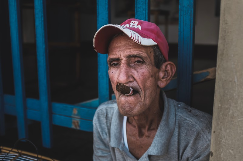 A Cuban sits in a touristy area of Trinidad, accepting photo requests from passersby (for a fee).