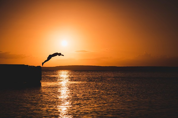A Cuban dives into the waters of the Bay of Cienfuegos during sunset.
