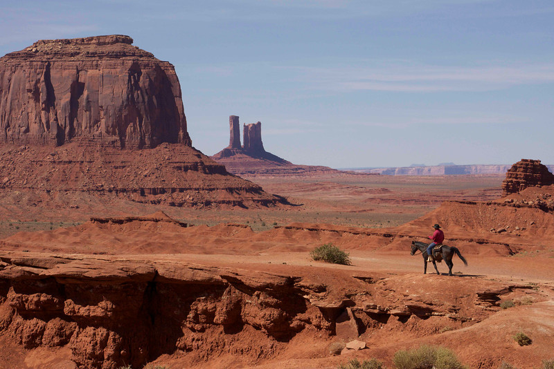 Navajo cowboy in Monument Valley. He mounts his horse and rides to the point every time a tour bus arrives. $2 to get on the horse to have your picture taken
