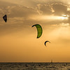 Silhouette of kites during sunset with rays of light in the background in kite beach.