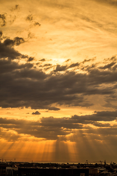 Rays of light through clouds in Dubai, UAE, hour before sunset. Portrait view