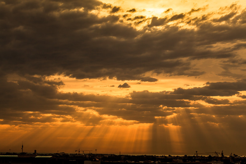 Rays of light through clouds in Dubai, UAE, hour before sunset. Landscape view