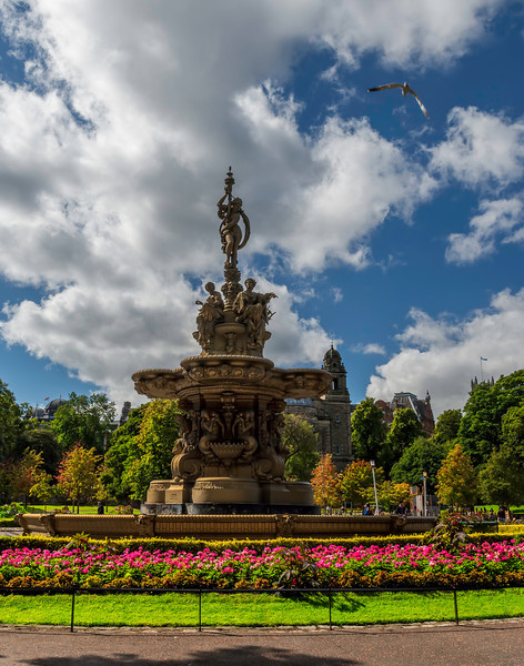 The Ross Fountain is a magnificent example of 19th century cast-iron work, from the foundry of Antoine Durenne 'Maitre de Forges, Sommevoire Haute Marne' in France.<br /> At ground level the circular basin has curved Craigleith sandstone edges, and the first elevated basin is decorated with stylised 'walrus' heads round the edge. <br /> The first tier of the central column has mermaid figures with overflowing urns, sitting on scallop-shell basins with lion's heads between. Swags and cornucopia abound, and the bowls above have cherub-faced spouts.