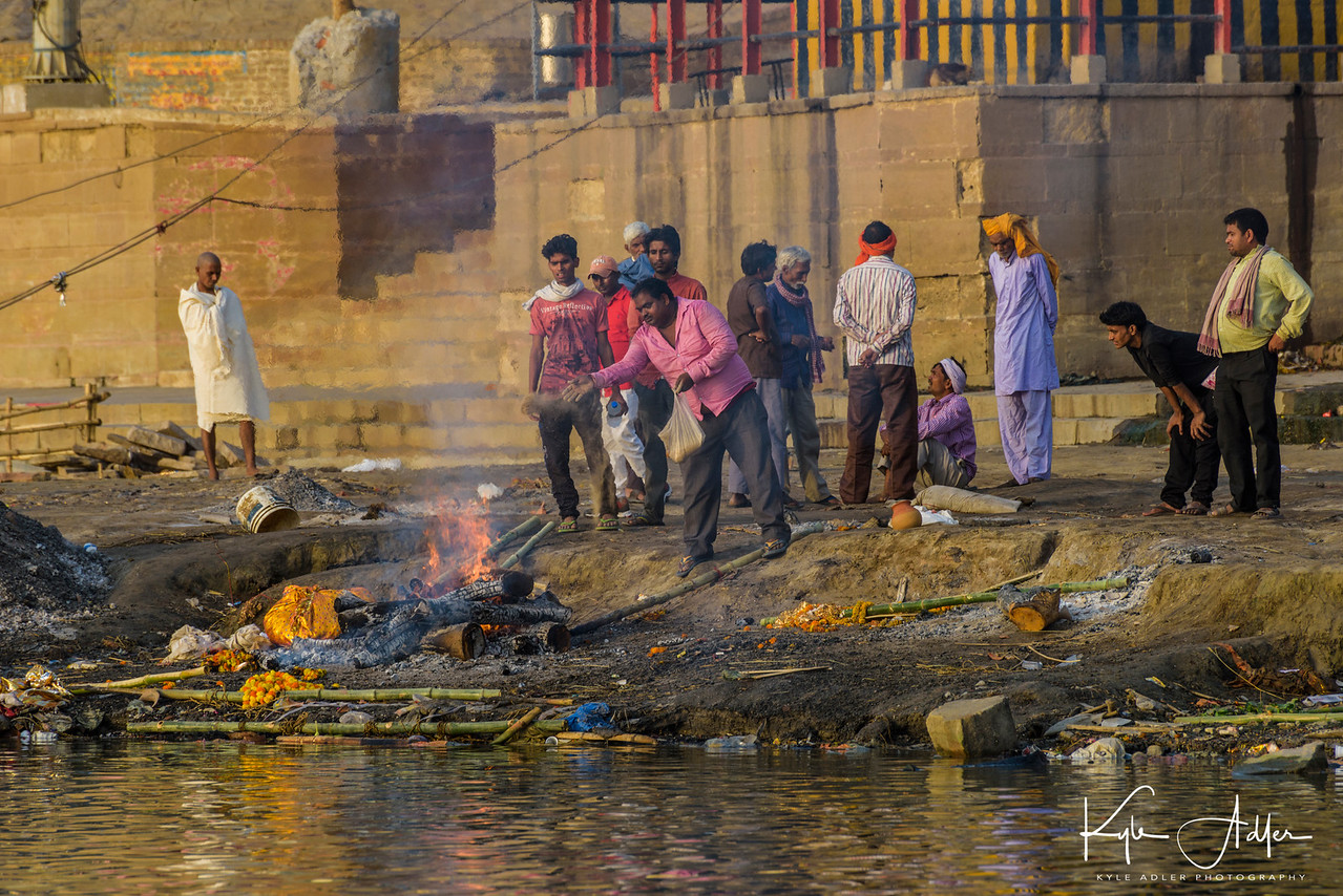 A cremation ghat (platform) along the Ganges in Varanasi.  Hindus believe that cremation in the Ganges River can end the cycle of death and rebirth.  The man on the far left in the image is the chief mourner for the family of the deceased.  The man in the center is a member of the untouchable caste, whose job is to tend to the cremation process.
