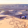Hiking to the top of a massive sand dune for happy hour at sunset in the Sahara.
