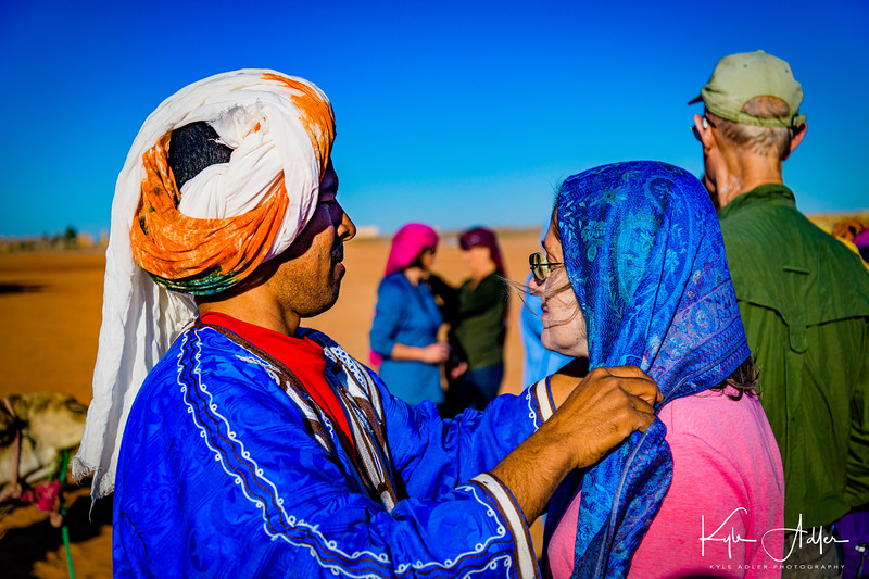 Our camel herder helps Mary wrap her scarf before boarding our dromedaries.