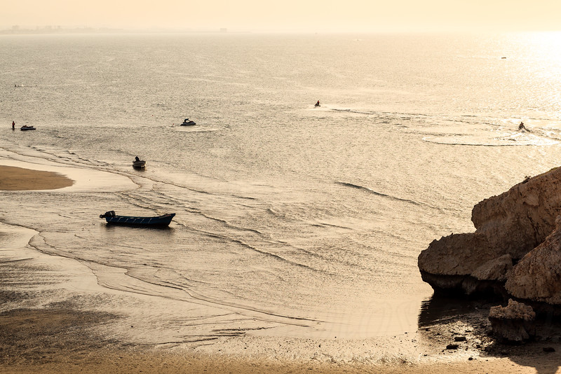 A fishing boat getting stuck in one of Muscat beaches in low tide with few tourists wandering around.