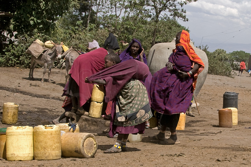 The women load the filled water jugs onto their backs to take them to their bomas which can be many hours away.