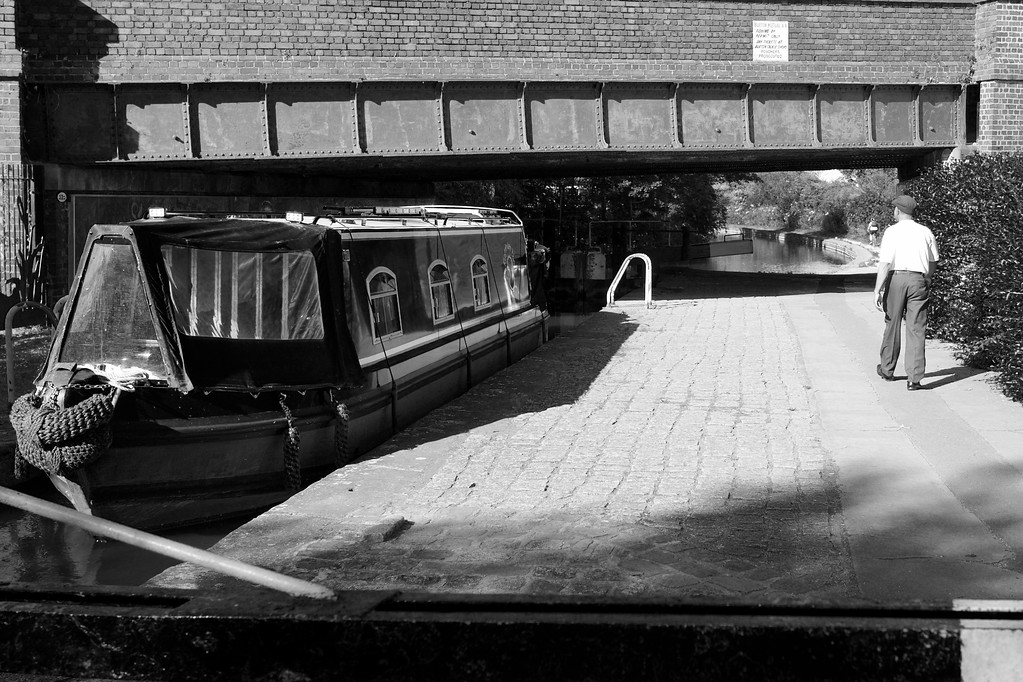 canal boat in a lock with a bridge above and a man walking past