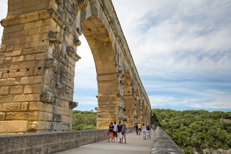 Tourists walking across the Pont du Gard