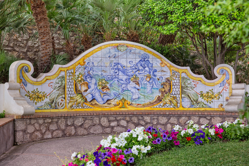 Ceramic bench between blooming flowers and mediterranean plants