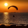Relaxing sunset in Ras Al Khaimah city of UAE with Persian Gulf sea and silhouette of a para-glider.