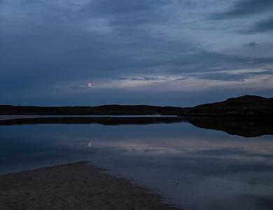 Moon sinks in the sky as the tide floods in