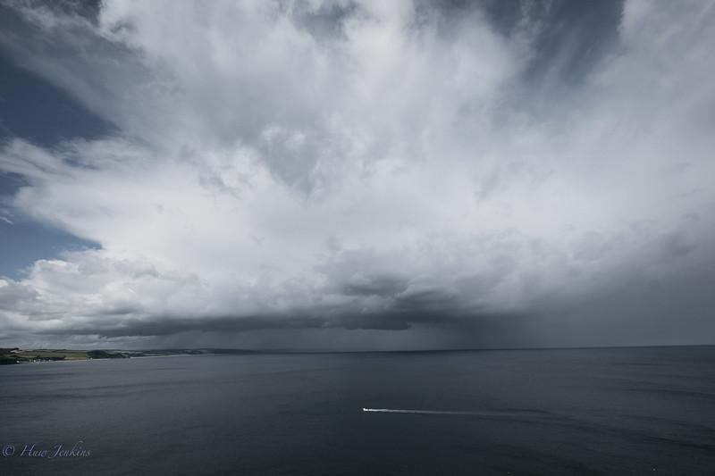 Small boat motoring across Freshwater Bay. Devon.