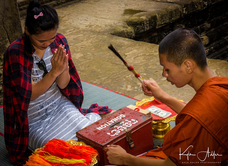 A Buddhist monk blesses a young woman at Angkor Wat.