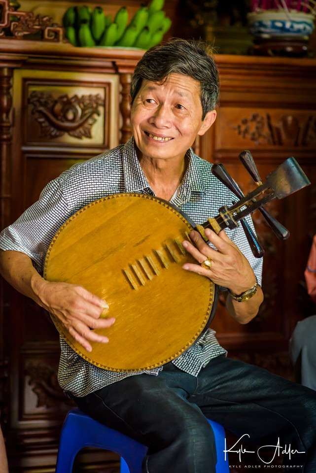 The head of the household plays a traditional Vietnamese stringed instrument.
