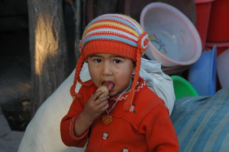 Little Uighur Girl Licking Walnut Shell - Kashgar, China