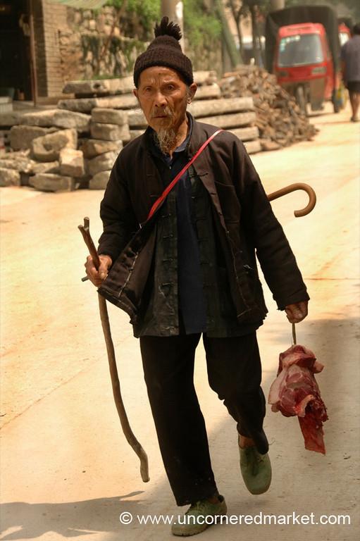 Man Carrying Meat to Market - Guizhou Province, China