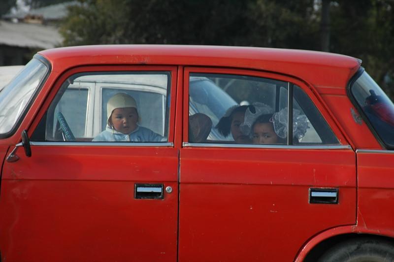 Kyrgyz Children in Red Car - Kochkor, Kyrgyzstan