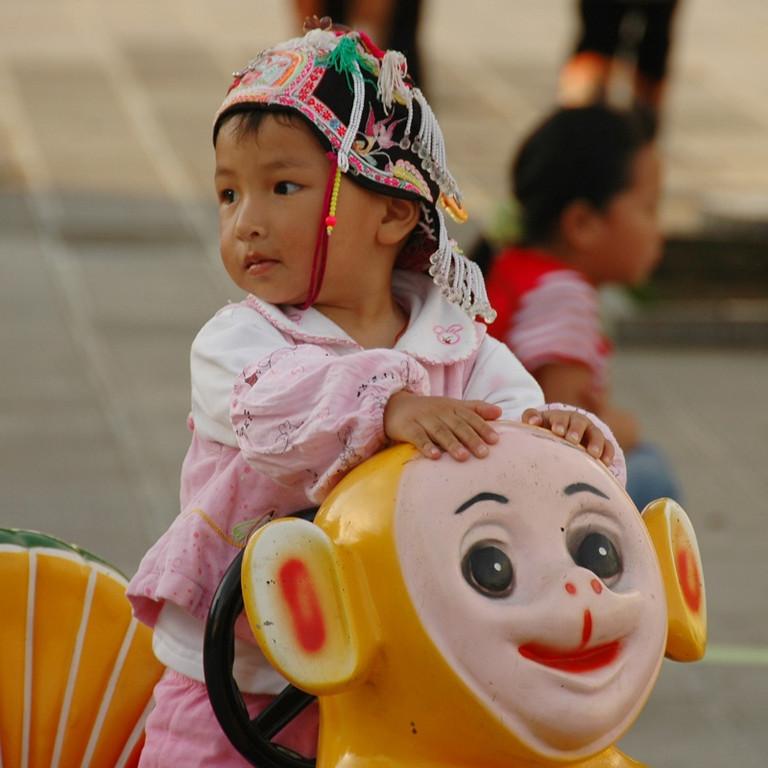 Little Hani Girl Riding a Teletubby - Yunnan, China