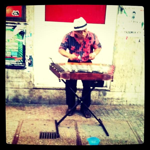 Street dulcimer musician in Neukolln, #Berlin. Playing away in the rain.