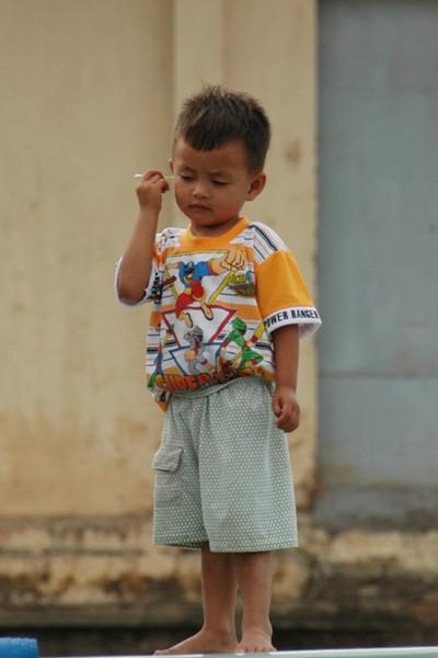 Boy Cleaning his Ear - Mekong Delta, Vietnam