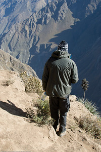 Tourist risking his life on a cliff edge waiting for a glimpse of an Andean condor. Colca Canyon, Peru.