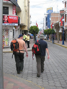Tourists on the prowl. Note the backpacks and the guidebook. Most tourists take a guidebook limited journey, afraid to do or experience anything that is not included in their guidebook. Consequently, they miss out on just about everything except the mega-tourist attractions. Otavalo, Ecuador.