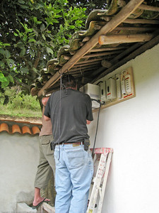 Installing the transformer distribution panel on the side of the campground shelter. This position allowed access to overlanders' vehicles parked on the hillside and the group camping area next to the shelter. It was also sheltered from the rains by the roof eve. Rincon del Viajero. Otavalo, Ecuador.