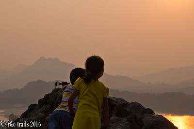 kids looking out over the mekong river at sunset
