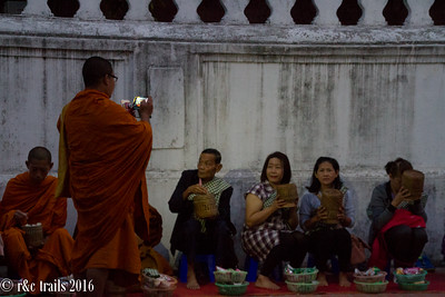 monk photographing alms-givers