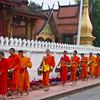 the monks of luang prabang receiving morning alms
