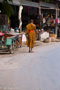 a monk walking the small town streets
