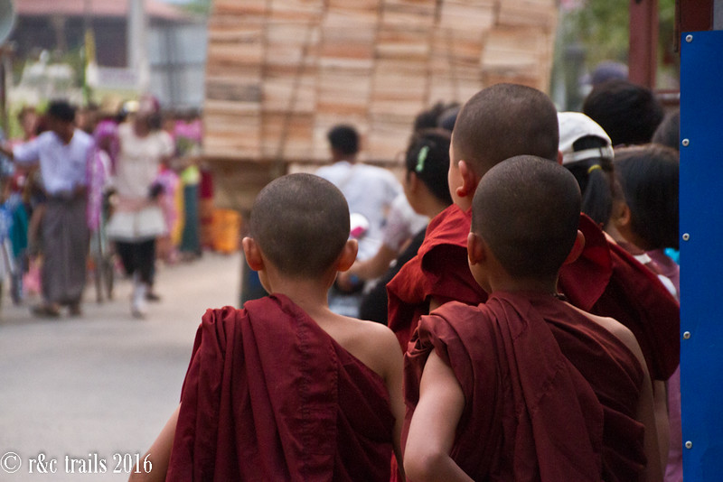 young monks looking on as the parade goes by