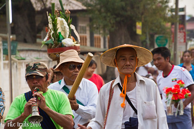 a parade for a young boy about to go to monk school. adults lead the procession.