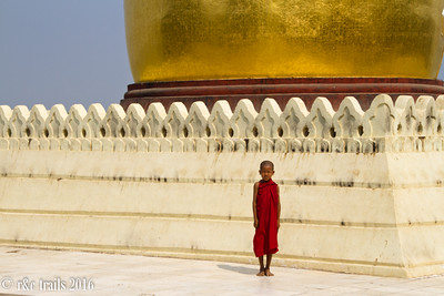 a young monk patiently posing in front of Bu Paya