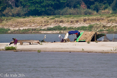a burmese man sanding his boat along the irrawaddy