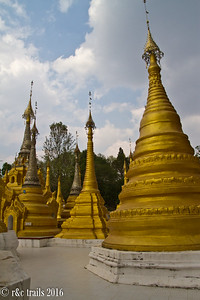 gold stupas at the grounds outside the caves