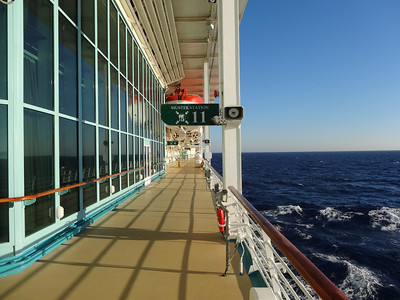 Ship has a large outdoor promenade deck with seats.