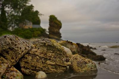 Rocks on the beach, Chito Beach Resort in background.