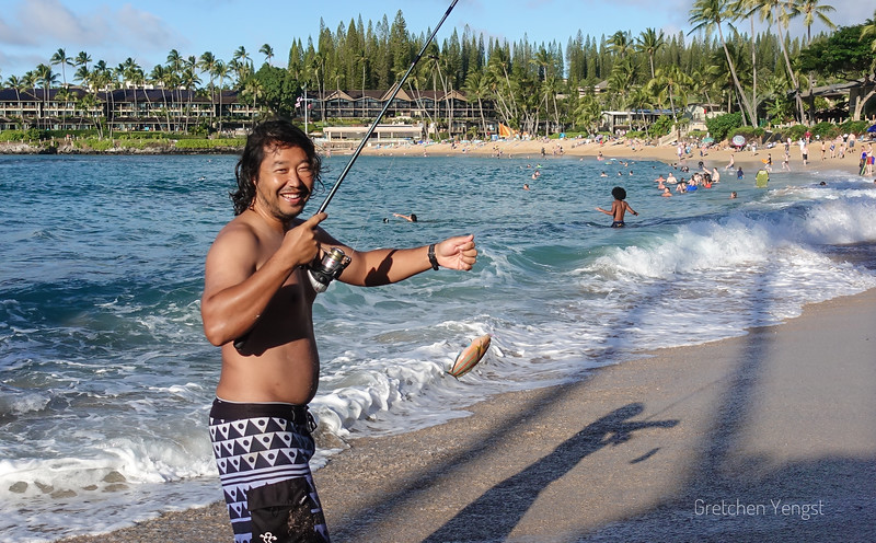 Here a local fisherman has caught a fish here off the Napili beach. He is ready to show me...