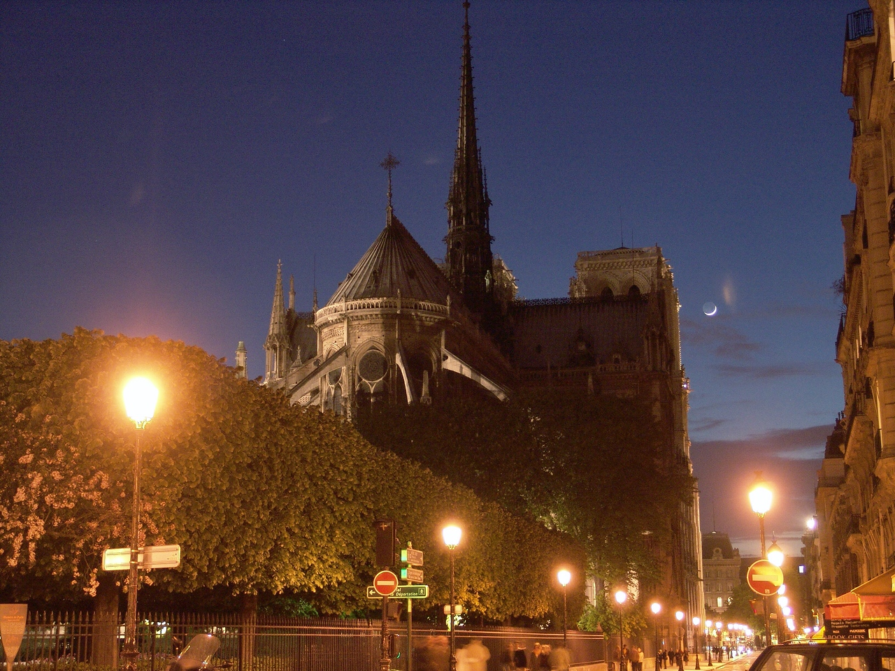 ND25: Here along the back side and Northern edge of the cathedral runs a boulevard...this photo captures a moonlit evening with Parisians out and about... going home from work or out to dinner.