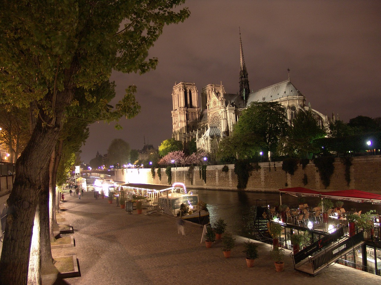 NDex1: Can you guess what these lit boats are doing here on the river parked across from the cathedral?? Answer: They are fancy restaurants for elegant and romantic dining.
