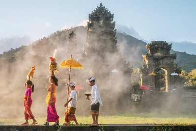 A Balinese family walking past a Hindu temple in Bali.