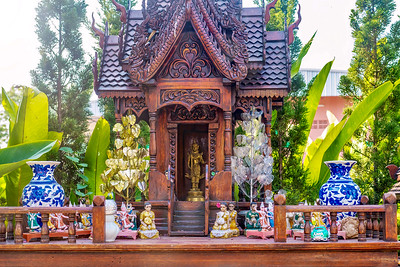 A Thai spirit house, a small replica of a traditional structure, where the deity or spiritual guardian of the property is believed to live, and offerings are made. Figurines represent spiritual attendants.