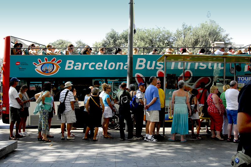 The tourist line up to board the city tour bus.